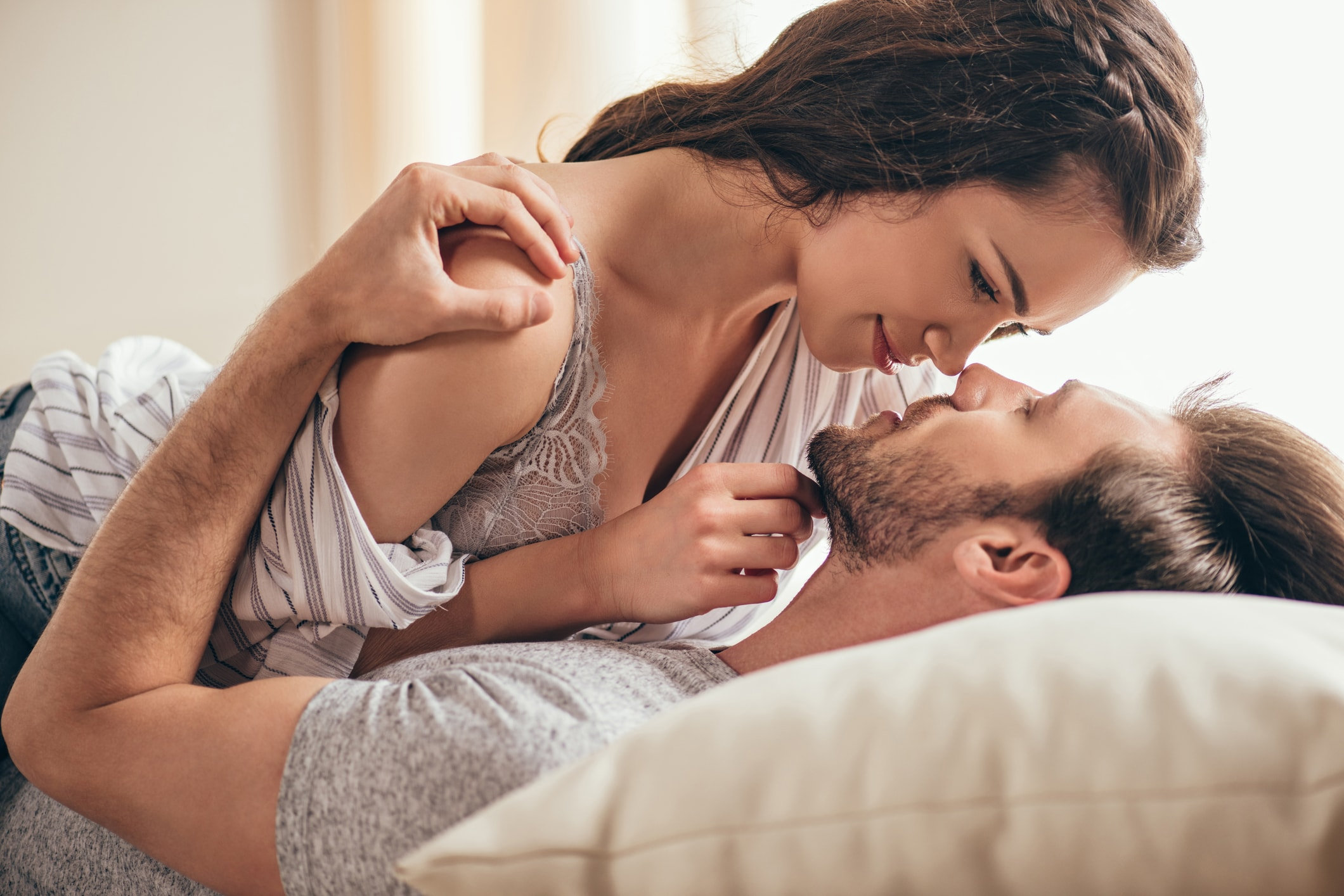 Close-up-portrait-of-beautiful-sensual-young-couple-hugging-while-lying-on-bed